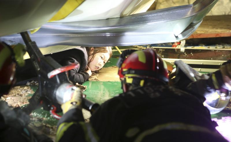 Firefighters try to rescue a university student trapped by debris from the collapsed resort in Gyeongju