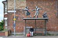 A graffiti artwork thought to be by Banksy shows a couple dancing to an accordion player above a bus stop (AFP/JUSTIN TALLIS)