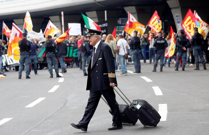 An Alitalia crew member walks past Alitalia employees who take part in a strike at Fiumicino international airport in Rome