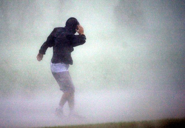 FILE - In this Thursday, Oct. 3, 2002, file photo, taken by Dave Martin, Jeff Gammons tries to walk against the wind and rain of Hurricane Lili as it neared landfall near New Iberia, Louisana. Martin, a longtime Associated Press photographer based in Montgomery, Ala., died after collapsing on the Georgia Dome field at the Chick-fil-A Bowl on Tuesday, Dec. 31, 2013. Martin was 59. (AP Photo/Dave Martin, File)