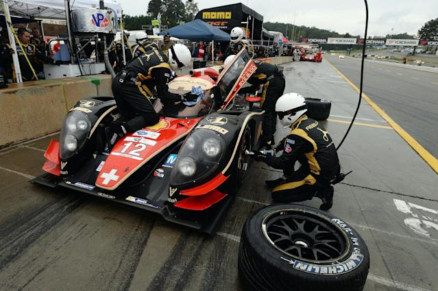 Driver Nick Heidfeld, of Germany, makes a pit stop as the Rebellion Racing team services his car during the American Le Mans Series' Petit Le Mans auto race at Road Atlanta, Saturday, Oct. 19, 2013, in Braselton, Ga. (AP Photo/Rainier Ehrhardt)