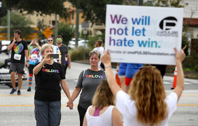 <p>Pulse nightclub owner Barbara Poma holds up a sign for runners passing her club during the CommUNITYRainbowRun 4.9K road race on Saturday, June 10, 2017, in Orlando, Fla. (Joe Burbank/Orlando Sentinel/TNS via Getty Images) </p>