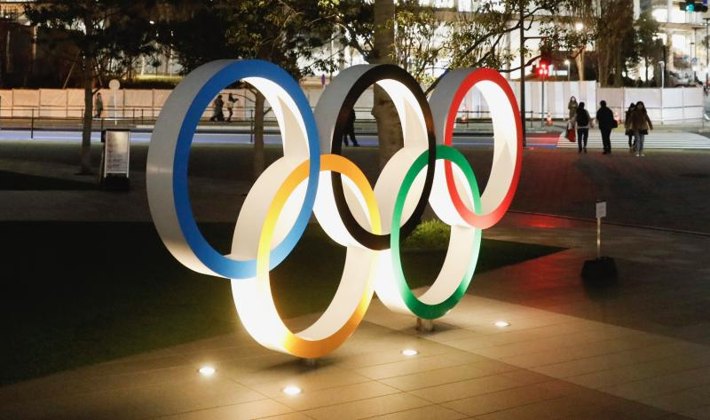 The Olympic rings stand near the new National Stadium Sunday, Dec. 15, 2019, in Tokyo.