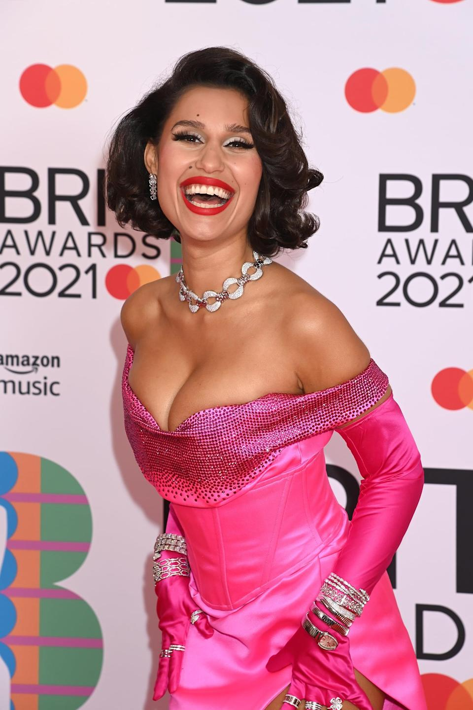 <p>Raye stunned in a powerful red lip, fluffy lashes, and a classic waved hairstyle to match her equally beautiful bright-pink gown. </p>