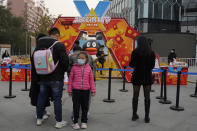 A child stands near a promotion event for Tencent in Beijing on Wednesday, Nov. 11, 2020. China is banning children from playing online games for more than three hours a week, the harshest restriction so far on the game industry as Chinese regulators continue cracking down on the technology sector. (AP Photo/Ng Han Guan)