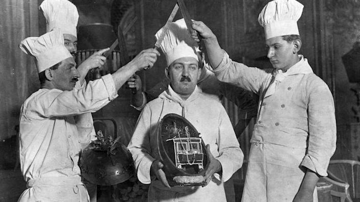 Chocolatiers cut into a giant chocolate egg (black and white photo)
