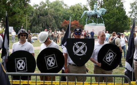 White supremacists gather under a statue of Robert E. Lee during a rally in Charlottesville, Virginia - Credit: Reuters