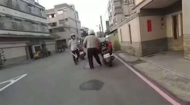 The aggressor wielding the baseball bat approaches the man after a close call on their scooters. Photo: YouTube