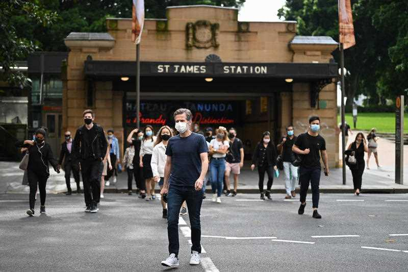 Commuters wearing face masks exit St James Station in the CBD in Sydney.
