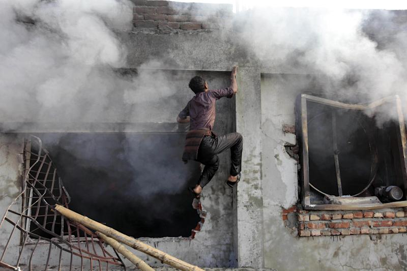 A Bangladeshi climbs a wall to get to the roof of a two-storied garment factory that caught fire in Dhaka, Bangladesh, Saturday, Jan. 26, 2013. The fire swept killed at least six female workers and injured another five, police and fire officials said. The latest fire occurred more than two months after a deadly fire killed 112 workers in another factory near the capital city, raising questions about the safety measures in Bangladesh garment industry. (AP Photo/A.M. Ahad)