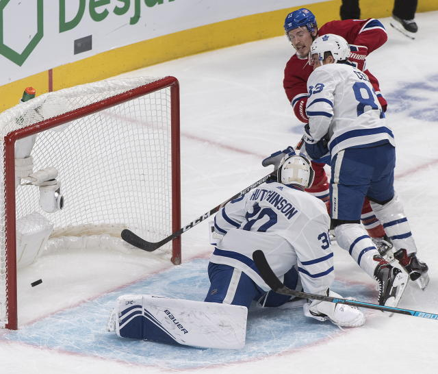 Montreal Canadiens' Brendan Gallagher (11) scores against Toronto Maple Leafs goaltender Michael Hutchinson as Leafs' Cody Ceci defends during the first period of an NHL hockey game, in Montreal, Saturday, Oct. 26, 2019. (Graham Hughes/The Canadian Press via AP)