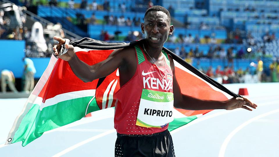 Conseslus Kipruto is seen here draped in the Kenyan flag after a race.