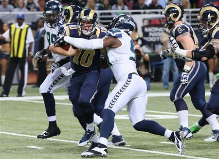 Oct 28, 2013; St. Louis, MO, USA; St. Louis Rams quarterback Kellen Clemens (10) rushes for a first down before being tackled by Seattle Seahawks defensive end Chris Clemons (91) during the first half at Edward Jones Dome. Mandatory Credit: Nelson Chenault-USA TODAY Sports