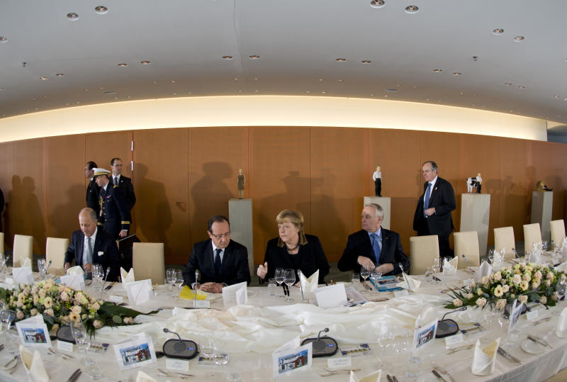 French Minister of Foreign Affairs Laurent Fabius, French President Francois Hollande, German Chancellor Angela Merkel and French Prime Minister Jean-Marc Ayrault, sitting from left, wait for the members of French and German governments prior to the French-German cabinet meeting in Berlin, Germany, Tuesday, Jan. 22, 2013, as part of the celebration to mark 50 years since the Elysee Treaty launched after WWII a French-German cooperation. (AP Photo/Odd Andersen, Pool)
