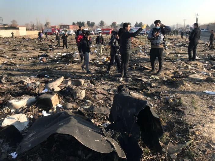 People check the debris from a plane crash belonging to Ukraine International Airlines after take-off from Iran's Imam Khomeini airport, on the outskirts of Tehran