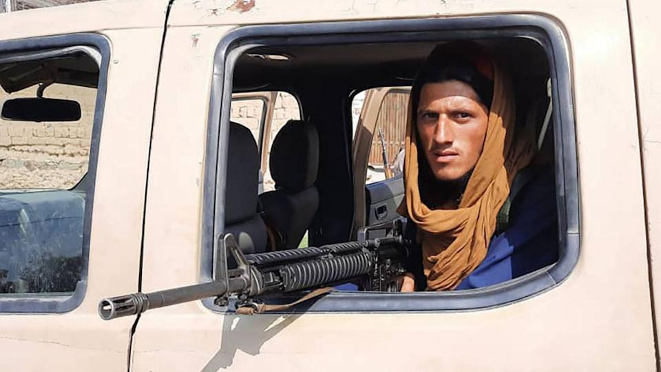 A Taliban fighter sits inside an Afghan National Army (ANA) vehicle along the roadside in Laghman province on August 15, 2021.