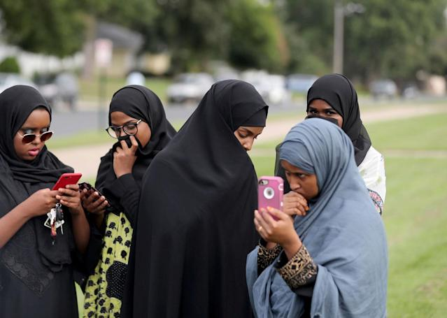 <p>People make phone calls as law enforcement investigate an explosion at the Dar Al-Farooq Islamic Center in Bloomington, Minn., on Saturday, Aug. 5, 2017. (Photo: David Joles/Star Tribune via AP) </p>