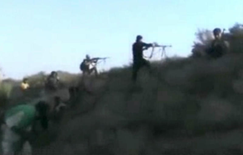 This image made from citizen journalist video posted by the Shaam News Network, which is consistent with other AP reporting, Syrian rebels fire at government forces at a military airport in Deir el-Zour, Syria, Monday, Oct. 28, 2013. The fighting coincided with the first visit to Syria by the U.N.-Arab League envoy Lakhdar Brahimi in almost a year. (AP Photo/Shaam News Network via AP video)