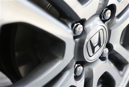 The logo of Honda Motor Co is seen on the wheel of a car outside the company showroom in Tokyo