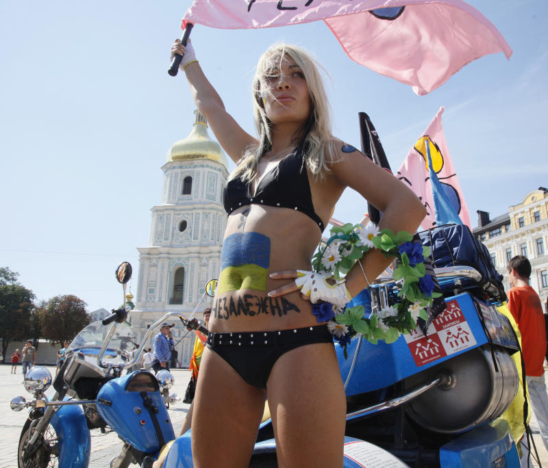 """In this photo taken on Tuesday, Aug. 24, 2010 an activist of a local women's rights watchdog FEMEN,  with writing """"I am independent"""" and Ukraine's' national flag on her belly, seen during celebrities on the occasion of Ukraine's 19th Independence in Kiev, Ukraine. How to fight against discrimination, poverty and water shortages? Take off your bra! A group of brazen young activists from a quasi feminist organization in Ukraine is gaining popularity for staging topless protests that involve sexually charged gestures, obscene slogans and police detentions. (AP Photo/Efrem Lukatsky)"""