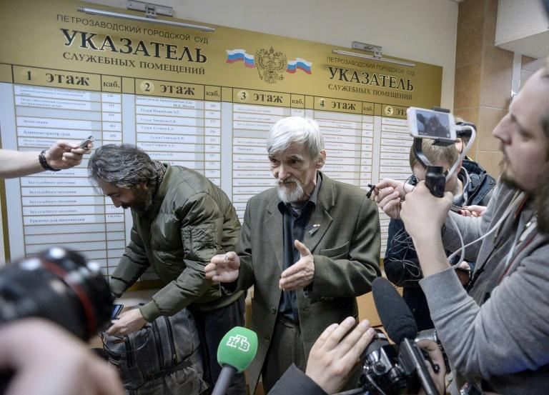 Russian historian Yury Dmitriyev (pictured April 2018), who heads rights group Memorial's branch in Karelia, speaks to the media as he leaves a court following the verdict in his child pornography trial in the northwestern city of Petrozavodsk
