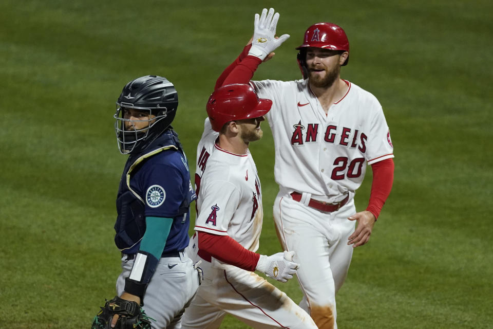 Los Angeles Angels' Taylor Ward, center, celebrates with first baseman Jared Walsh (20) after they both scored off of a home run hit by Ward during the sixth inning of a baseball game against the Seattle Mariners Saturday, June 5, 2021, in Anaheim, Calif. Seattle Mariners catcher Jose Godoy, left, reacts. (AP Photo/Ashley Landis)