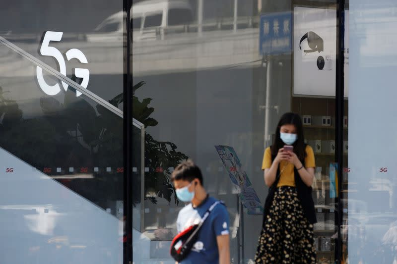 Woman uses a mobile phone outside a Huawei store with a 5G sign in Beijing