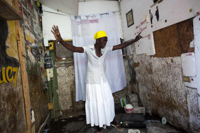 "In this Dec. 6, 2018 photo, Marie-Lourdes Corestan asks herself out loud how will she survive without her son, in his room after he was slain during the La Saline massacre in Port-au-Prince, Haiti. Corestan, a 55-year-old mother of three, said a group of men arrived in a police truck in the afternoon on Nov. 13 wearing police uniforms and ski masks, some carrying machetes. ""They were shooting, and I was running to save my life,"" she said. (AP Photo/Dieu Nalio Chery)"
