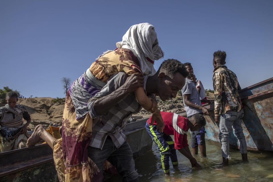 Tigrayan refugees who fled the conflict in the Ethiopia's Tigray arrive on the banks of the Tekeze River on the Sudan-Ethiopia border, in Hamdayet, eastern Sudan, Tuesday, Dec. 1, 2020. (AP Photo/Nariman El-Mofty)