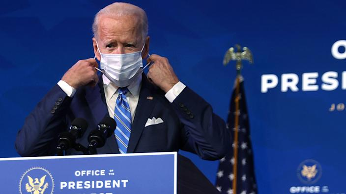 President-elect Joe Biden takes off his mask before presenting his plan to combat COVID-19 and boost the economy on Thursday.