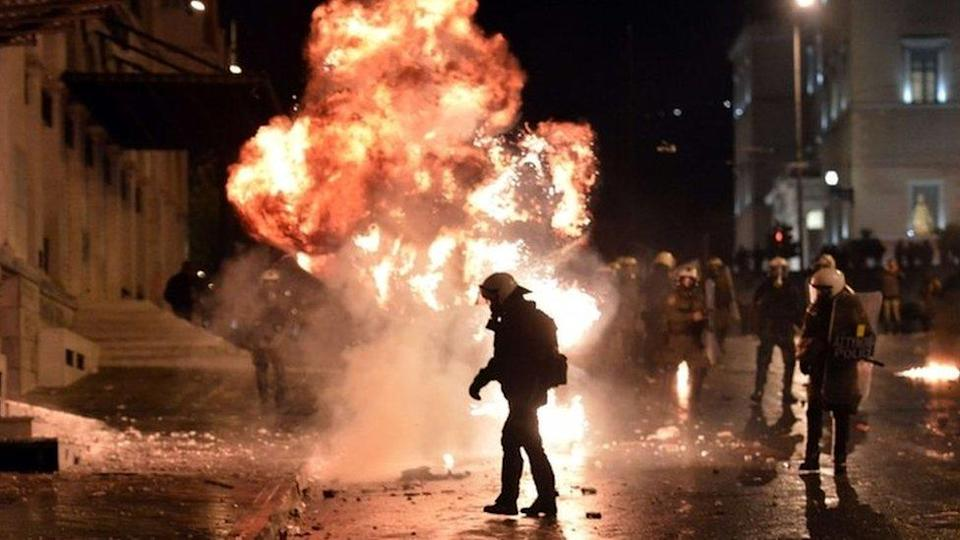 A petrol bomb explodes next to riot police in Athens. Photo: 7 November 2012