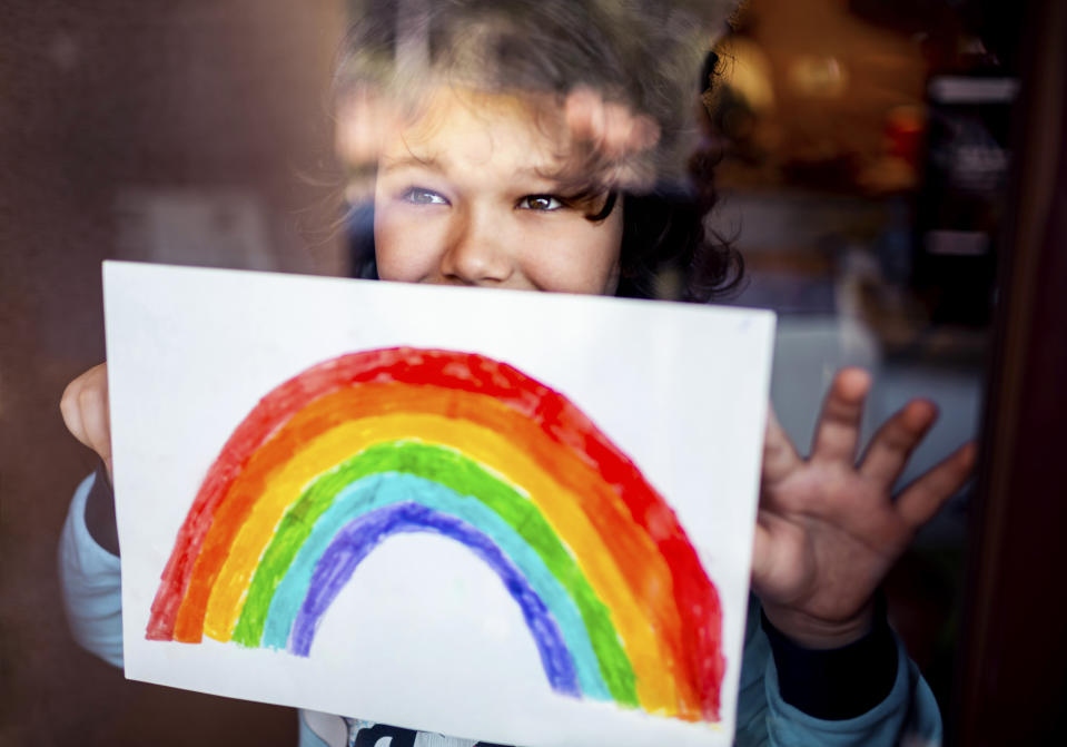 Close up of a little boy putting his rainbow painting on the window during Covid-19