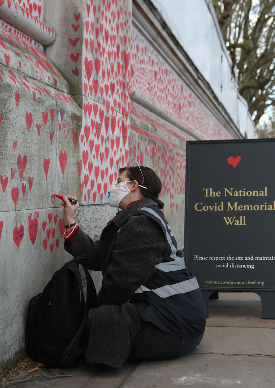 A volunteer adds hearts to the National Covid Memorial Wall in Westminster, central London