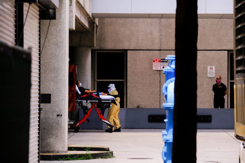 Emergency Medical Technicians (EMT) arrive with a patient to Jackson Health Center, where the coronavirus disease (COVID-19) patients are treated, in Miami
