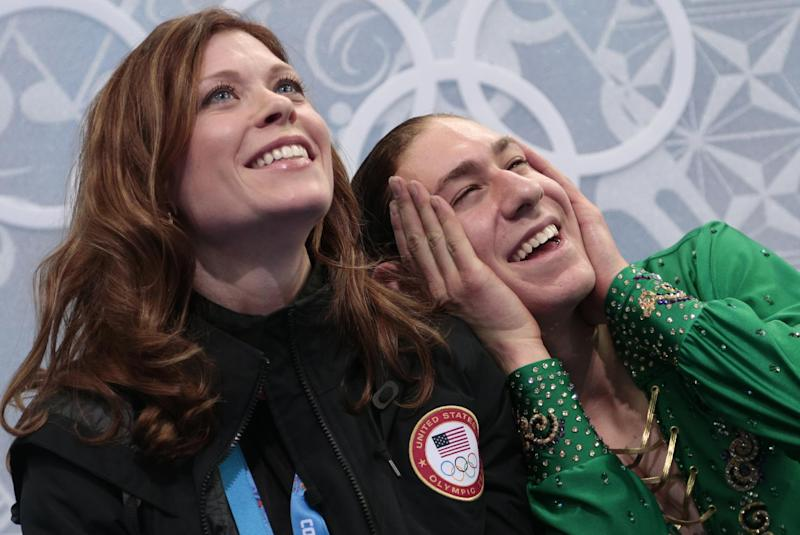 Jason Brown of the United States, right, reacts as he sits alongside his coach Kori Ade in the results area after the men's free skate figure skating final at the Iceberg Skating Palace at the 2014 Winter Olympics, Friday, Feb. 14, 2014, in Sochi, Russia. (AP Photo/Ivan Sekretarev)