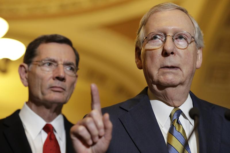 Senate Majority Leader Mitch McConnell of Kentucky, right, accompanied by Sen. John Barrasso, Republican of Wyoming