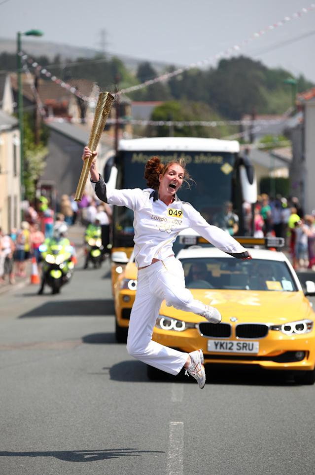 BRYNMAWR, UNITED KINGDOM - MAY 25: In this handout image provided by LOCOG, Synchronised swimmer Nadine Struijk of the Netherlands jumps while carrying the Olympic Torch on May 25, 2012 in Mrynmawr, Wales. The Olympic Torch is on the seventh day of it's journey around the United Kingdom which will involve 8,000 torchbearers covering 8,000 miles. (Photo by LOCOG via Getty Images)