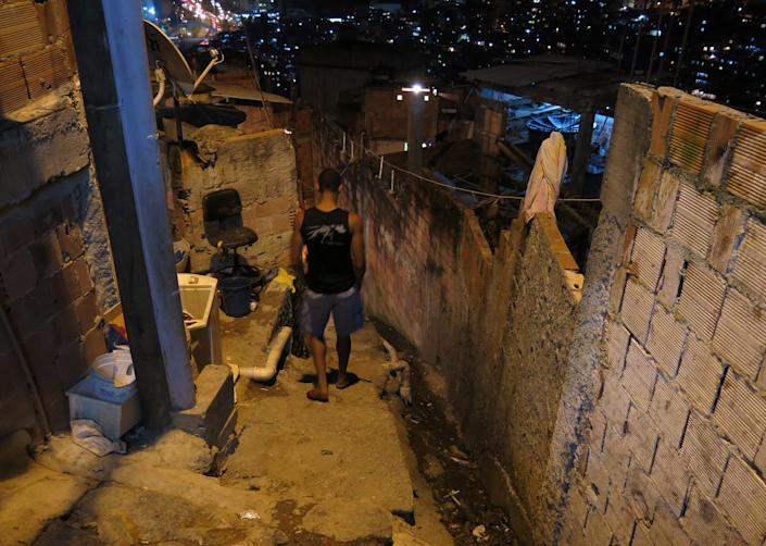 """In this Oct. 1, 2013 photo, Amarildo de Souza's son, Anderson, descends a set of exterior steps near his home in the Rocinha slum, in Rio de Janeiro, Brazil. De Souza disappeared in July after last being seen in police custody in Rocinha slum. Investigators said they've recommended to prosecutors that 10 police officers from the slum's """"pacifying"""" unit be charged with de Souza's abduction, torture, death and disappearance of his body. (AP Photo/Bradley Brooks)"""