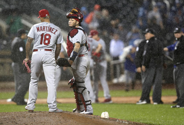 St. Louis Cardinals catcher Yadier Molina looks toward the New York Mets' dugout as he and Cardinals relief pitcher Carlos Martinez (18) stand on the mound awaiting a decision on whether to resume play during the ninth inning of a baseball game Thursday, June 13, 2019, in New York. The game was suspended due to the rain, and is scheduled to resume Friday. (AP Photo/Kathy Willens)