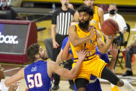 Arizona State guard Remy Martin, right, passes the ball around Houston Baptist center Ryan Gomes (50) during the first half of an NCAA college basketball game, Sunday, Nov. 29, 2020, in Tempe, Ariz. (AP Photo/Rick Scuteri)