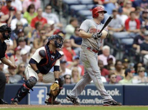 Cincinnati Reds right fielder Jay Bruce follows through for a two-run home run as Atlanta Braves catcher Gerald Laird, left, looks on in the third inning of a baseball game Sunday, July 14, 2013 in Atlanta. (AP Photo/John Bazemore)