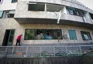 A man removes debris at a hospital damaged by shelling by Azerbaijan's artillery in Stepanakert, the separatist region of Nagorno-Karabakh, Wednesday, Oct. 28, 2020. Nagorno-Karabakh officials said Azerbaijani forces hit Stepanakert, the region's capital, and the nearby town of Shushi with the Smerch long-range multiple rocket systems, killing one civilian and wounding two more. (AP Photo)