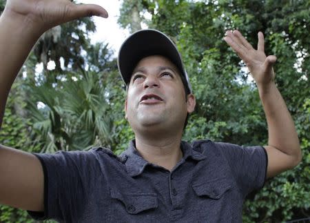 Alain Izquierdo, a Havana butcher and one of 15 survivors of the 32 Cuban migrants who were left adrift in Caribbean waters during their voyage, gestures while speaking with Reuters at his uncle's home in Port St. Lucie, Florida, October 3, 2014. REUTERS/Rickey Rogers (UNITED STATES - Tags: POLITICS SOCIETY IMMIGRATION DISASTER)