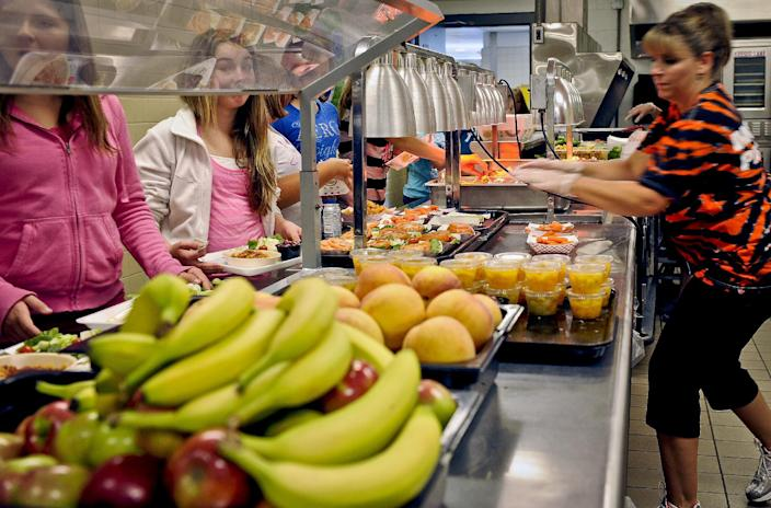 FILE - In this Tuesday, Sept. 11, 2012 file photo, students are given healthy choices on a lunch line at Draper Middle School in Rotterdam, N.Y. After just one year, some schools across the nation are dropping out of what was touted as a healthier federal lunch program, complaining that so many students refused the meals packed with whole grains, fruits and vegetables that their cafeterias were losing money. (AP Photo/Hans Pennink, File)