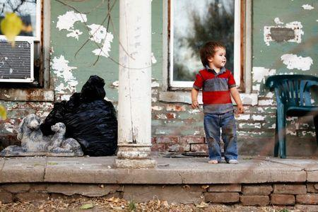 Kadin Mignery, 2, plays on the front porch of his home in St. Joseph, Missouri, U.S. November 15, 2016. REUTERS/Whitney Curtis