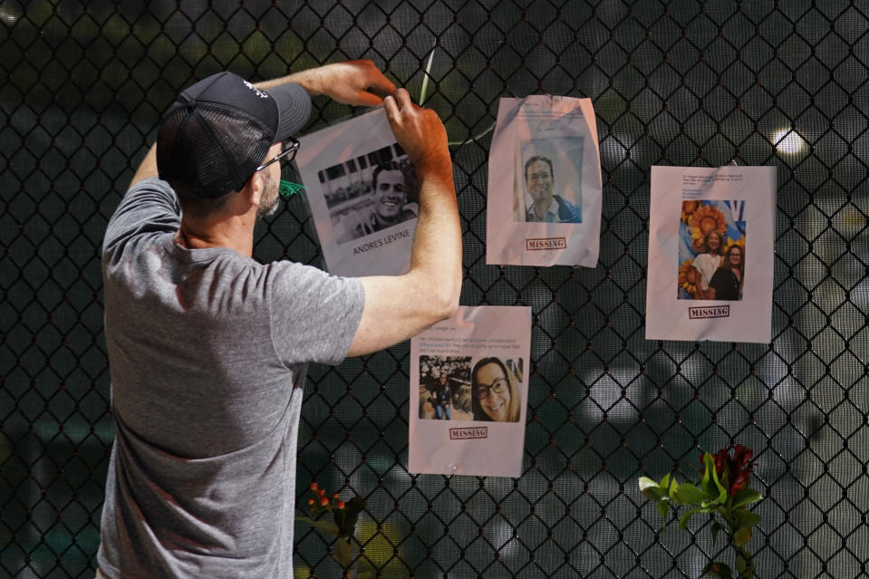 A man hangs a photo on a fence of someone missing near the site of an oceanfront condo building that partially collapsed in Surfside, Fla., Friday, June 25, 2021. (AP Photo/Gerald Herbert)