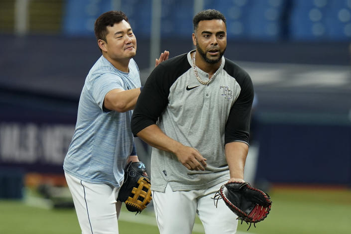 Tampa Bay Rays first baseman Ji-Man Choi, left, pats Nelson Cruz on the back during an American League Division Series baseball practice Wednesday, Oct. 6, 2021, in St. Petersburg, Fla. The Rays play the Boston Red Sox in the best-of-five series. (AP Photo/Chris O'Meara)