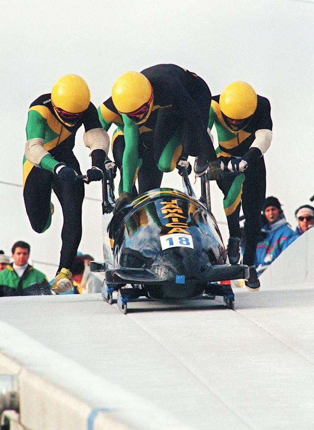 <p>Jamaican pilot Dudley Stokes jumps in as his three teammates push off at the start of the second run of the Olympic four-man bobsled event at the Calgary Olympics in 1988. (Getty Images) </p>