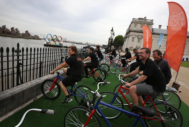 People cycle to power Olympic rings fountains installed on The River Thames at Greenwich on August 1, 2012 in Greenwich, England. (Photo by Peter Macdiarmid/Getty Images)