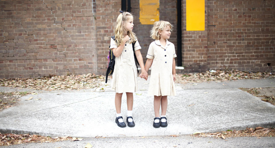Two little girls in school uniforms wait to cross the road. Source: Getty Images